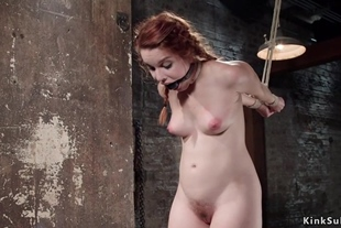 Redhead in backbend bondage whipped